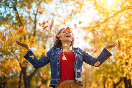 Porträt einer glücklichen Frau, die mit Herbstlaub im Wald spielt. Herbstkonzept