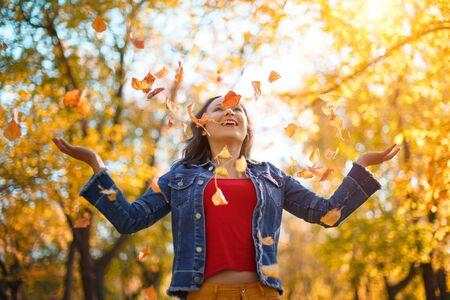 Portret szczęśliwa kobieta bawi się jesiennymi liśćmi w lesie. koncepcja jesień
