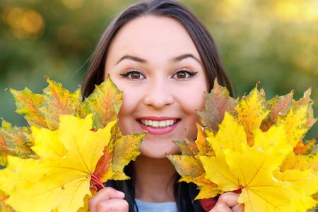 Portrait of smiling young woman with autumn leafs in front of foliage. season. autumn concept