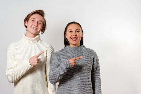 a happy guy and a girl in sweaters stand next to each other and point their index finger to the right. Place under the copyspace Reklamní fotografie