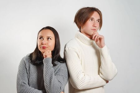 Female and male standing near each other having pensive expressions trying to find solution. Two best friends in casual clothes pondering about something while standing against white background