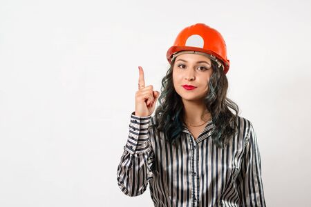 Woman builder in helmet points finger at copy space on white background.