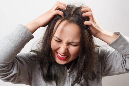 una giovane donna si gratta il cuoio capelluto e i capelli con le dita. Concetto di salute dei capelli, cuoio capelluto e cura dei capelli