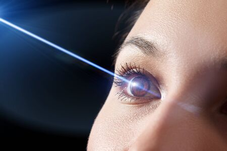 woman's eye close-up. Laser beam on the cornea. Concept of laser vision correction, ophthalmology Stockfoto