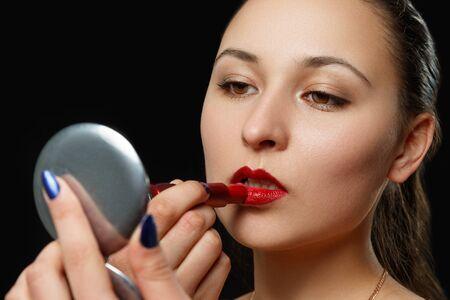 una mujer joven se pinta los labios con lápiz labial rojo sobre un fondo negro. foto de belleza, maquillaje, moda