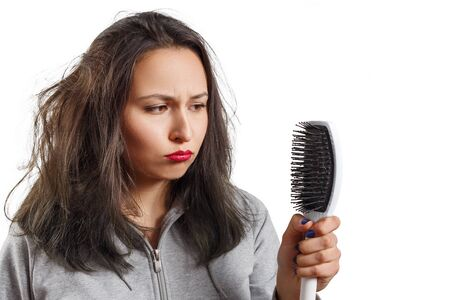 a girl with tousled shaggy hair holds a comb in her hands. hair, scalp and dandruff problems isolated on white Stock Photo