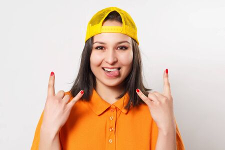 young funny teen girl in bright clothes shows gesture goat. on white background