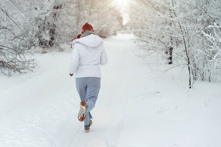 Running sport woman. Female runner jogging in cold winter forest wearing warm sporty running clothing and gloves. Beautiful fit Caucasian female fitness model.