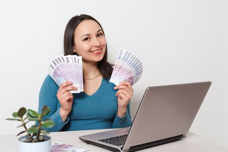 Young cheerful woman holding fan of cash money ibanknotes, sit and work at desk with pc laptop on white background. Achievement business career lifestyle concept. Mock up copy space