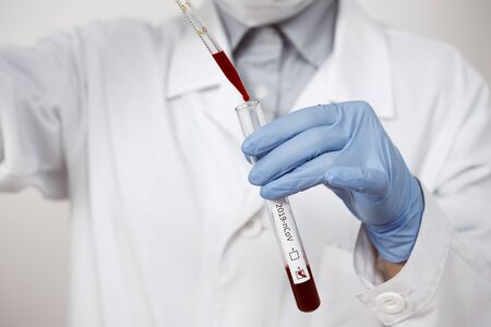 Coronavirus Covid 19 infected blood sample in sample tube in hand of scientist doctor biohazard protection clothing in coronavirus covid 19 research laboratory, Coronavirus Covid-19 vaccine research