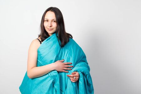 A happy young girl wrapped up in a blue blanket. on white