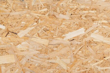 Oriented Strand Board. Chipboard building material. OSB wooden panel made of pressed sandy brown wood shavings as background closeup