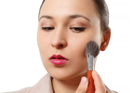 a young woman puts makeup on her face with a brush. on white background. close up