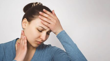 Portrait of a young woman holding her hands to her temples with a severe headache. On light background. Migraine, high blood pressure, cardiovascular system. Banque d'images