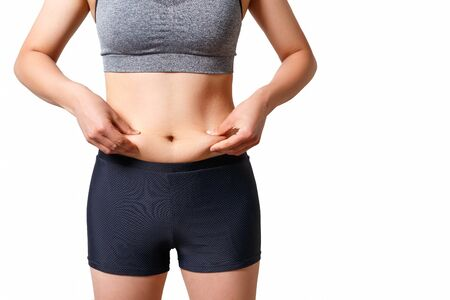 the woman presses her fingers to the folds of fat on the sides of her stomach. on white background