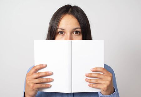 young woman girl holds a book in front of her, and peeks out because of her