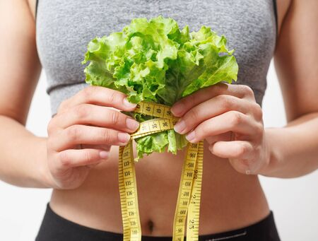 lettuce and a measuring tape in the hands of a woman. on white background.