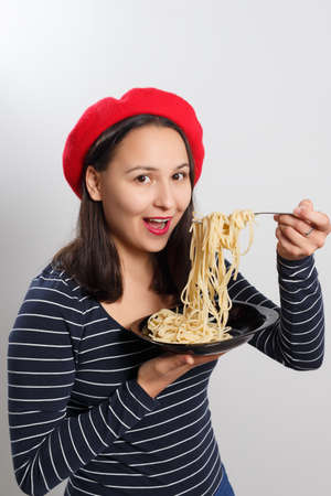 Young woman in a red beret eating spaghetti close-up. On white background.
