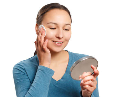 Young woman wipes her face with a cotton pad with lotion, looking at the mirror and smiling. Isolated on white background.