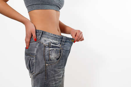 Woman after losing weight in old big jeans. Isolated on white background. Banco de Imagens