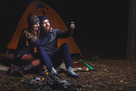 tent: Couple tent camping in the wilderness taking selfie Stock Photo