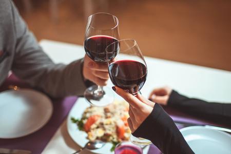 person sitting: Pareja joven hermosa con vasos de vino tinto en restaurante de lujo