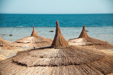 el sheikh: Vacation holidays background wallpaper -  beach lounge chairs under tents on beach. Egypt hotel Sharm El Sheikh Stock Photo