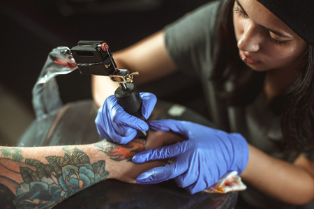Beautiful brunette girl makes tattoo. Tattooist makes a tattoo. Closeup