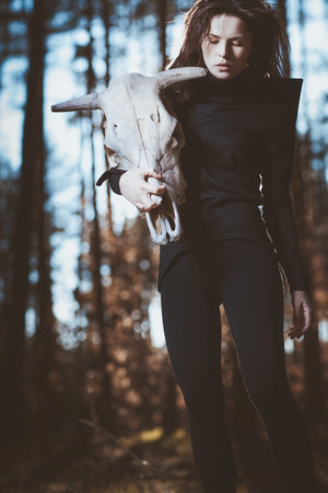 evil skull: Young witch with skull in night forest