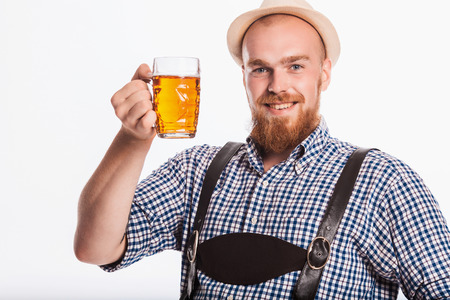 suspender: Happy smiling man with leather trousers (lederhose) holds oktoberfest beer glass. Isolated on white background Stock Photo