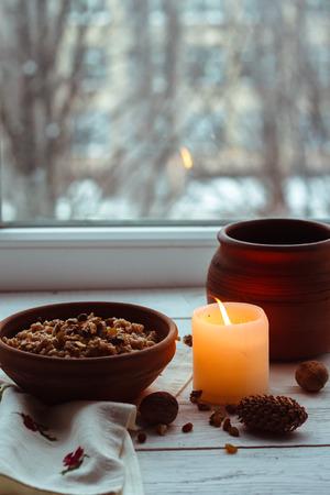 Christmas porridge with candles on white wooden background Stock Photo