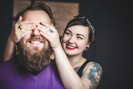 couple cuddling: young couple in love with tattoos having fun, the girl closes hands eyes guy