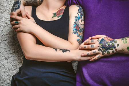 cuddling: young couple in love, tattoos, cuddling and holding hands on the bed Stock Photo