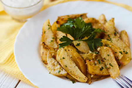 rosmarin: beautiful roasted potatoes with herbs and spices on a white plate