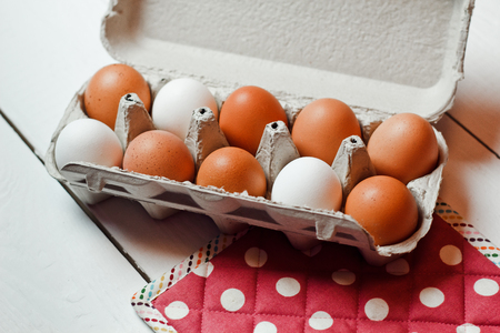 albumen: Beautiful chicken eggs with red napkin on white wooden background Stock Photo