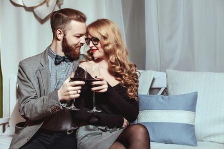 美しい若いカップルと高級レストランで赤ワインのガラス