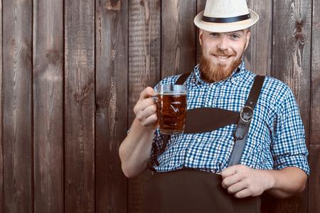 革のズボン (lederhose) 新鮮なビールを試飲、幸せな笑みを浮かべて男。
