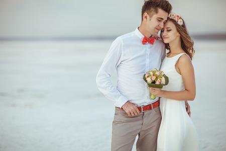 カップルは、ビーチの上を歩きます。結婚式