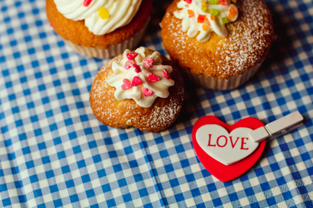 scattered in heart shaped: Beautiful cupcakes and a heart with the inscription Love lie on a vintage checkered tablecloth Stock Photo