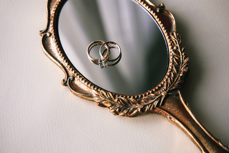 shine background: Beautiful wedding rings on a vintage mirror Stock Photo