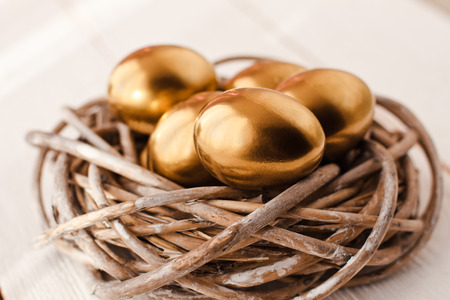 golden light: Golden easter eggs in nest on white wooden background