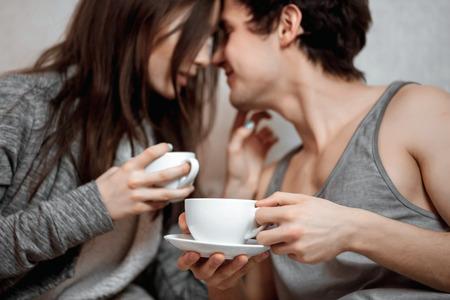 恋人たちの若い美しいペアは、ベッドでお茶 (コーヒー) を飲みます。優しさと愛情の概念 写真素材