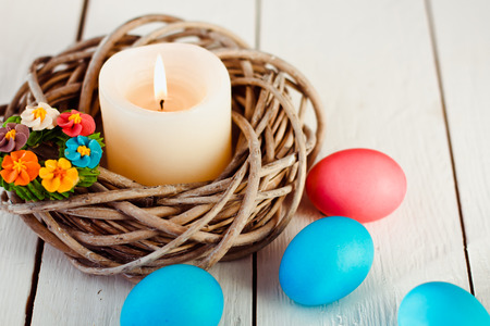easter candle: Easter background with candle in a nest of twigs and colored eggs on white wooden background