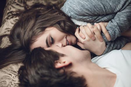 nackter junge: schöne Brünette Mädchen und Jungen im Bett liegen und eng Hand in Hand. Das Konzept der Zärtlichkeit und Zuneigung
