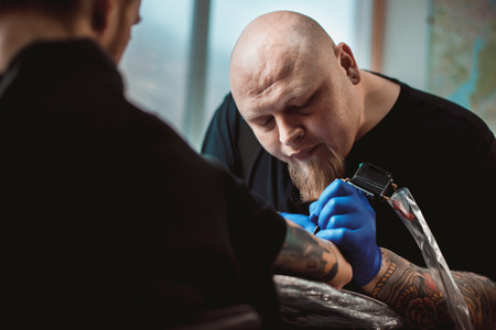 master tattoo artist with a beard makes gloves tattoo on hand men Reklamní fotografie - 55155307