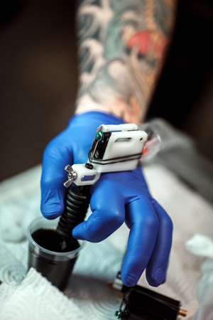 tattooing: master tattoo artist prepares tools for tattooing