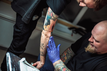 tattooing: master tattooist gets a healing ointment on the skin after the tattooing