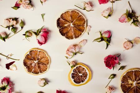 バラやドライフラワーで美しい背景が白い背景の上に置いたレモンの輪切りを乾燥