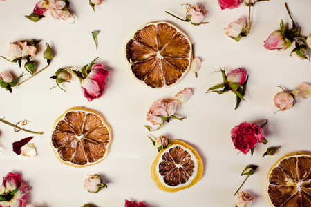 Beautiful background with roses and dried flowers dried round slices of lemon laid on a white background