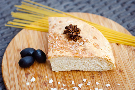 black olives: Fresh bread and spaghetti with black olives on Board Stock Photo
